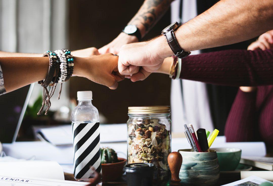 Hands fist-bumping over work desk