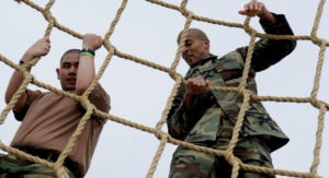 110316-N-KK330-369 SAN DIEGO (March 16, 2011) - Chief Special Warfare Operator David Goggins climbs the cargo net obstacle with 15 year-old George Alvarado, a Make-A-Wish Foundation recipient. Alvarado, who underwent a heart transplant last year, realized his dream of being a Navy SEAL, as he toured Naval Special Warfare facilities with Goggins, who also endured two heart surgeries during his career. The Make-A-Wish Foundation is a charity organization that allows children with life threatening illnesses to live their dreams. (U.S. Navy photo by Mass Communication Specialist 2nd Class Dominique Lasco/Released)